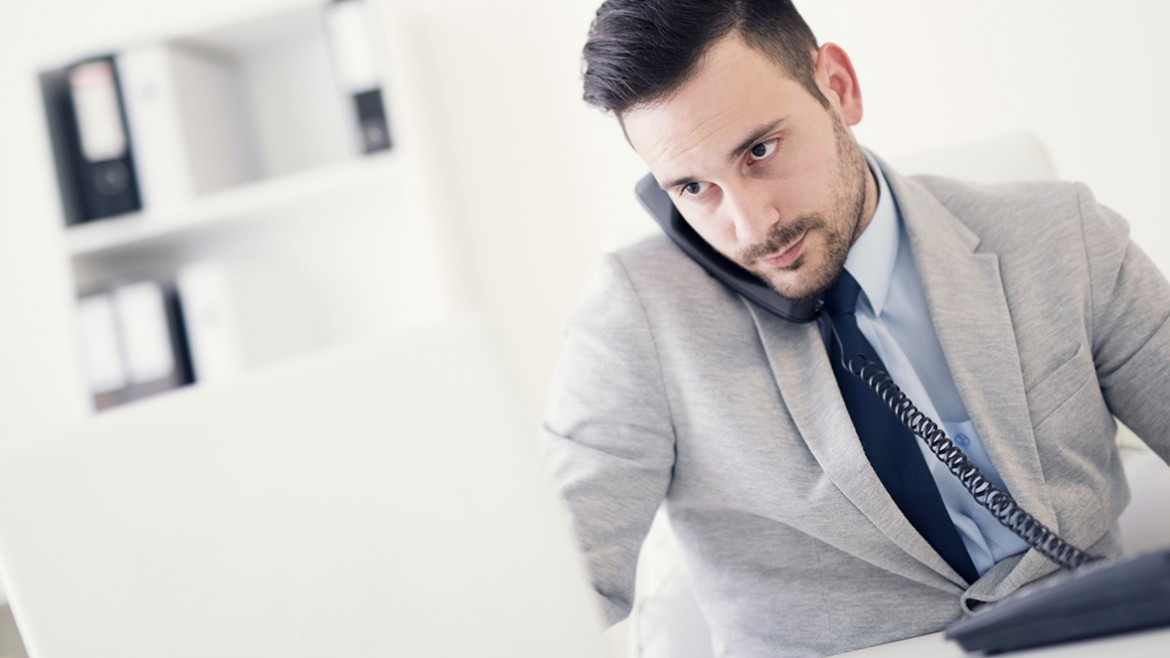 Businessman on phone while using computer in the office